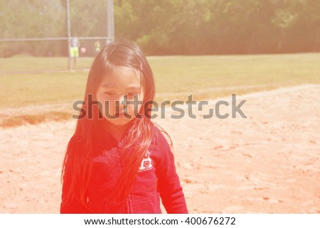 A closed up of lovely little girl playing sand at public park with soccer goal background ,filtered color tone in picture. - stock photo