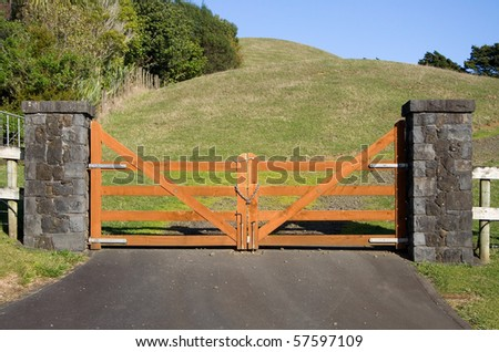 A closed wooden gate on a vacant paddock in the New Zealand countryside - stock photo