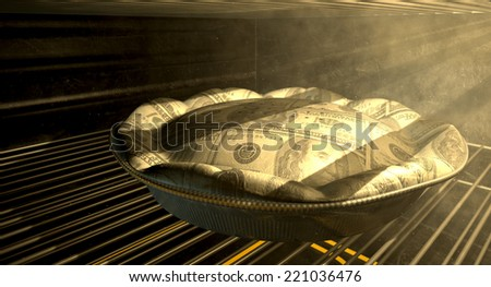 A closeup concept of a money pie made with US Dollar bank notes baking in a heated oven