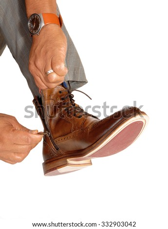 A closeup image of a man putting on his brown boots, pulling up thezipper of the shoe, isolated for white background. - stock photo
