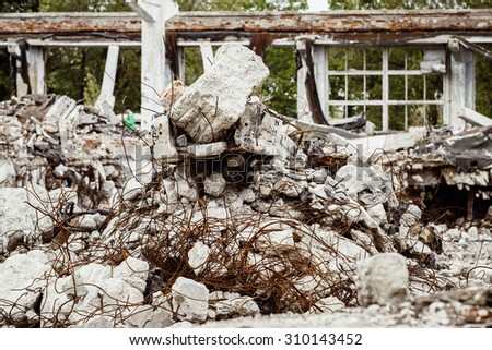 A closeup image of a ruined building with concrete and armature around. Concept of disaster, war. - stock photo