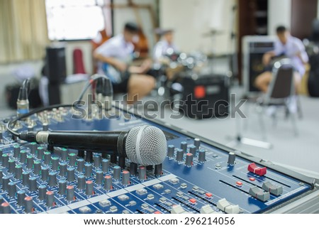 A closeup image of microphone on audio mixer's on musician blurred background - stock photo