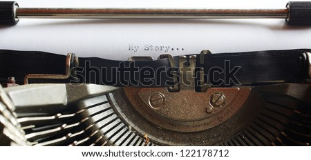 A Closeup image of the typebars and ribbon of an old style typewriter and paper with the text: My Story... (Shallow Depth of Field) in a panorama crop - stock photo
