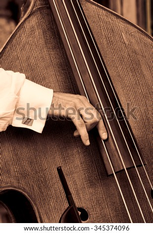 A closeup of a bass fiddle with the hand of the musician.