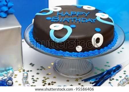 A closeup of a birthday cake and presents. - stock photo