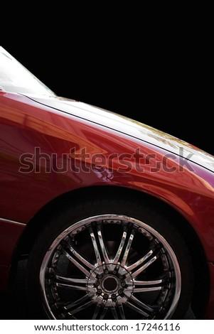 A closeup of a chrome rim on a modern luxury sedan, isolated over black. - stock photo