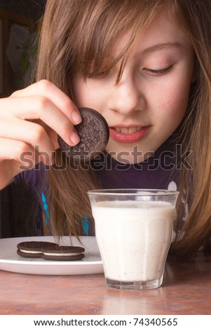 A closeup of a cute girl dipping a chocolate cookie in milk - stock photo