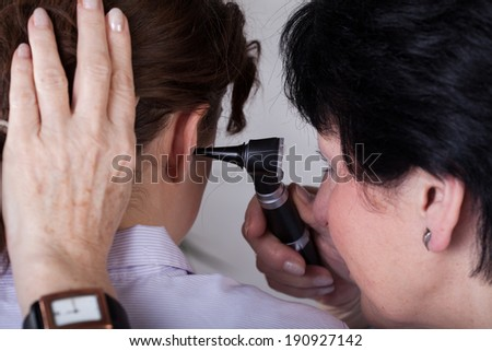 A closeup of a doctor examining her patient's ear - stock photo