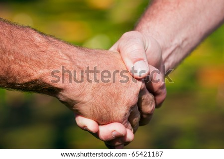 A closeup of a friendly handshake between two men - stock photo