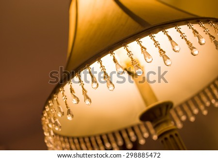 A closeup of a lampshade with crystal tassels cropped for an artistic presentation.  Focus is on the tassels and the lamp is turned on.