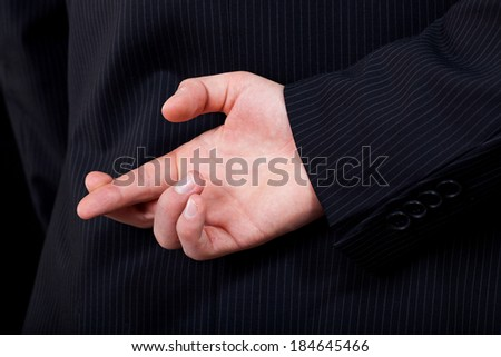 A closeup of a man doing a cheating gesture with his hand