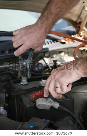 A closeup of a mechanics hands using jumper cables on a car battery. - stock photo