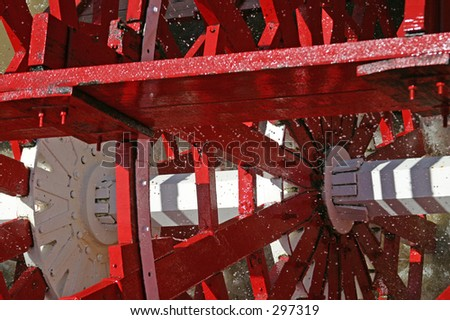 A closeup of a paddle wheel, captured in motion with water churning and spraying through it. - stock photo
