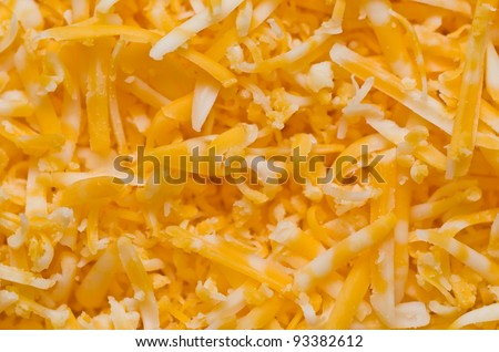 A Closeup of a Pile of Shredded Cheddar Cheese - stock photo