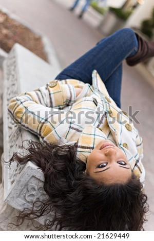 A closeup of a pretty Indian woman laying on a bench outdoors. - stock photo