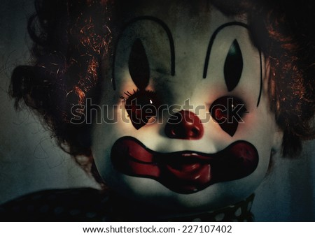 A closeup of a scary evil clown toy doll that could be possessed with evil. Use it for a halloween or fear concept. - stock photo