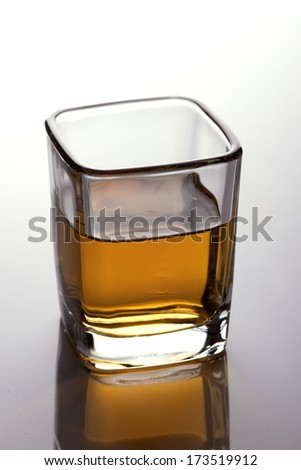 A closeup of a shot-glass partially full of an alcoholic drink on white