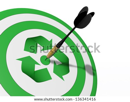 a closeup of a target with a green recycle symbol in the center and a perfect shot of a dart in the middle of it - stock photo