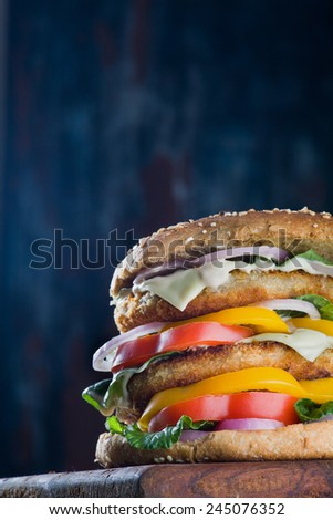 A closeup of a tempting tasty burger with seafood patty and fresh vegetables on dark background. With copy space - stock photo