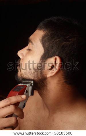 A closeup of a young man trimming his beard with an electric trimmer