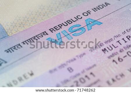 "A closeup of an Indian business visa vignette inside a passport.  Shallow DoF with focus on the word ""VISA"". - stock photo"