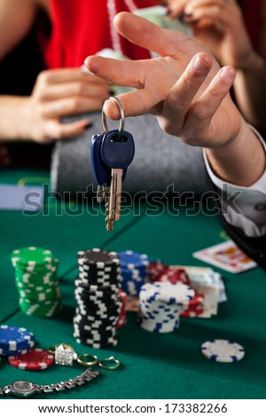 A closeup of car keys above a gambling table - stock photo