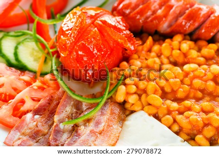 A closeup of continental breakfast containing sausages, bean truck, bacon, fresh vegetables, fried eggs and bread. - stock photo