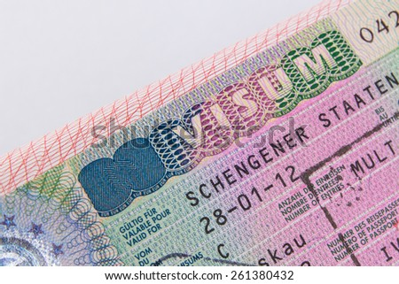 A closeup of German multi schengen visa tourist visa vignette inside a passport. Shallow DoF with focus on the word VISUM single with immigration stamp macro - stock photo
