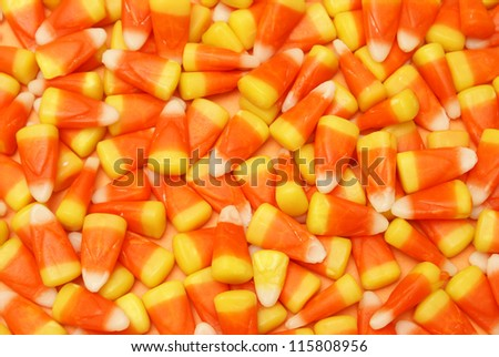 A closeup of many pieces of candy corn. - stock photo