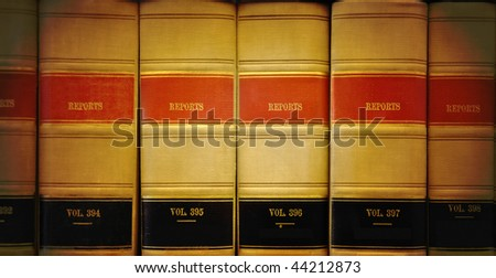 A closeup of old looking law books in a library on a shelf. The lighting is on the center. Colors are brown, red and black. - stock photo