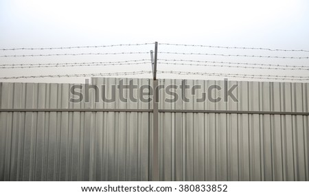 A closeup of perimeter fencing with barbed wire and construction fence against the sky - stock photo