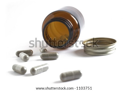 A closeup of some pills pouring out of a prescription bottle
