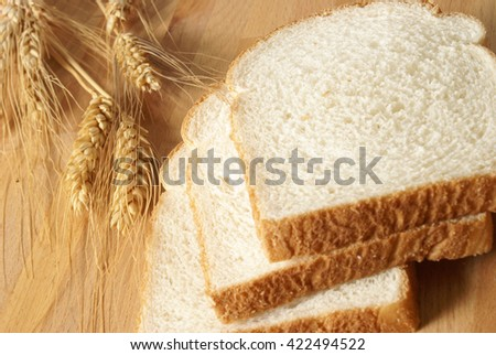 A closeup of some wheat and sliced bread. - stock photo