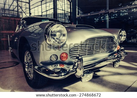 A closeup of the headlights and front bumper on a vintage automobile. - stock photo