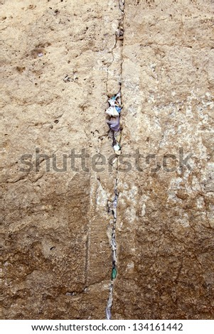 A closeup of the Wailing Wall in the old city of Jerusalem. In the cracks between the bricks there are numerous notes with pleads and requests from people to the Hebrew God. - stock photo