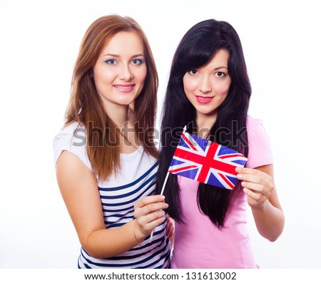 A closeup of two young smiling girls holding a British flag  isolated on white.