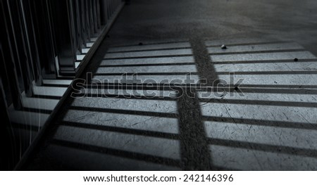 A closeup of view of a jail cells iron bars casting shadows on the prison floor with copy space - stock photo