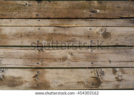 A closeup of weathered wooden dock planks with sand sprinkled on them. - stock photo