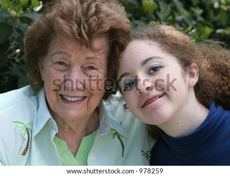 A closeup portrait of a sweet grandmother and cute teen granddaughter. - stock photo
