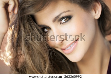 A closeup portrait of a young happy woman with beautiful eyes. Fashion and beauty concept in studio.  - stock photo