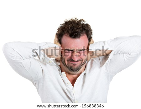 A closeup portrait of a young man holding hands to ears covering to shut out noise, looking stressed and pushed to the limit, isolated on a white background . Human emotion extremes  - stock photo