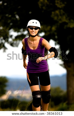 A closeup portrait of a young woman running on the roller skates in the country - stock photo