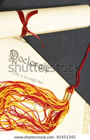 A closeup shot of a doctorate and diploma scroll with the tassels of a mortar board. - stock photo