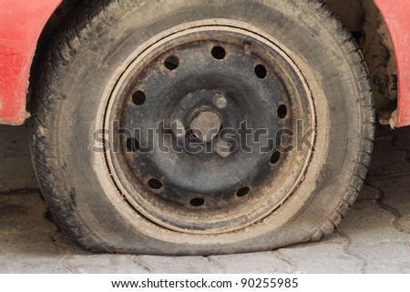 A closeup shot of a flat tire of a car - stock photo