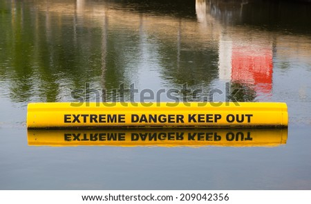 A closeup to a sign which is warning of extreme danger in the water - stock photo