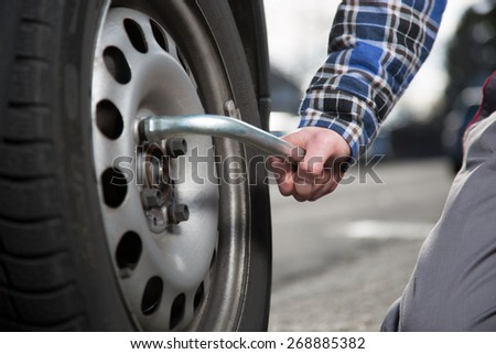 A closeup view from a mechanic who is unscrewing a tire screw. - stock photo