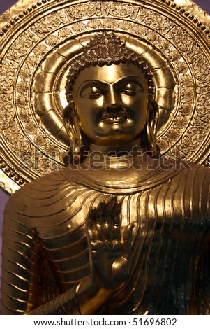 A closeup view of a golden statue of Lord Buddha.