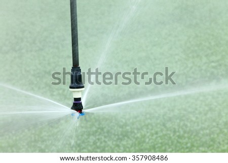 A closeup view of a high tech agricultural sprinkler head water farm crops. - stock photo