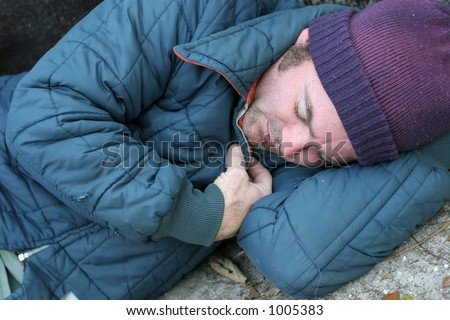 A closeup view of a homeless man sleeping on the ground. - stock photo