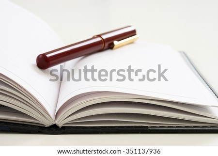 A closeup view of an elegant pen on top of an open journal with blank white pages. - stock photo